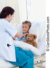 Young female doctor listening to a child chest and a teddy bear
