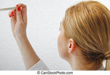 Young female doctor looking at thermometer
