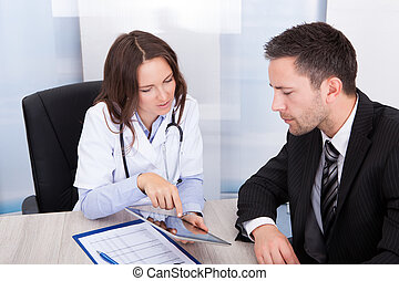Young Female Doctor Showing Digital Tablet To Businessman