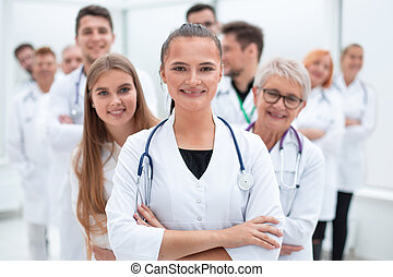young female doctor standing in front of her older colleagues.