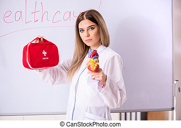 Young female doctor standing in front of the white board