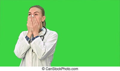 Young female doctor tired, yawning and suffering from headache on a Green Screen, Chroma Key.