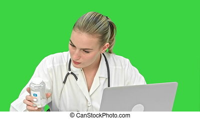Young female doctor typing on laptop, trying to find a manual of pills in the Internet on a Green Screen, Chroma Key.