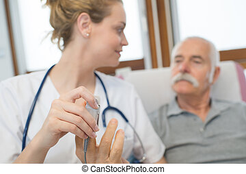 young female doctor using lancelet on senior male patients finger