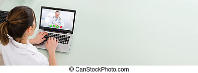 Female Doctor Video Chatting On Laptop