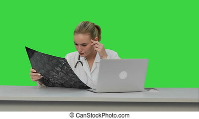 Young female doctor worried because of difficult case of patient she saw in xray on a Green Screen, Chroma Key.