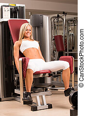 Young female doing leg exercises on a machine at the gym