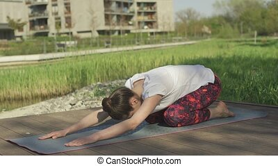 Young female doing yoga outdoors near home - nonymous...