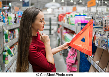 Young female driver buys warning triangle in the supermarket car department.
