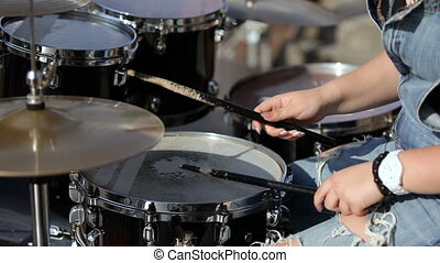 young female drummer plays drums. close-up - young female...
