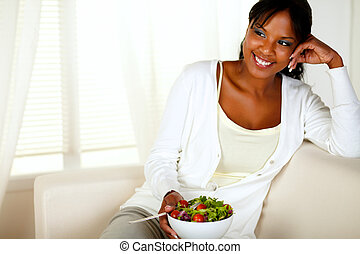 Young female eating healthy salad lunch