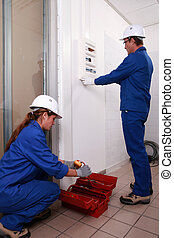 young female electrician and mature instructor looking at electric meter
