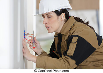 young female electrician installing electrical socket on wall