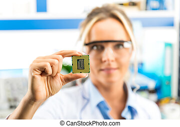 Young female electronic engineer holding CPU in hand