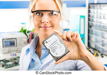 Young female electronic engineer holding HDD in hand