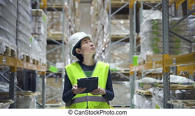 Young female employee walking on storehouse room and using tablet while working.