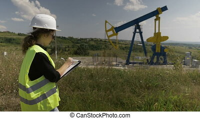 Young female engineer doing research near an oil pump unit...