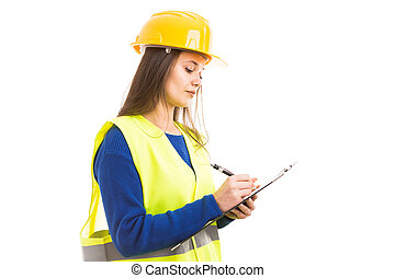 Young female engineer writing on clipboard