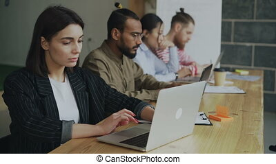 Young female entrepreneur freelancer working and using laptop computer at busy coworking office. Businesswoman and team concentrated on technology project