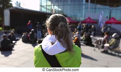 slow motion view from the back of a young female environmentalist listening to speeches at a protest with crowd and government building in background