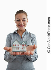 Young female estate agent presenting miniature house