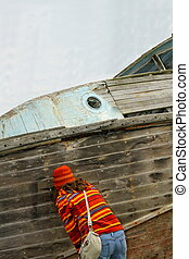 Young female examines abandoned boat.