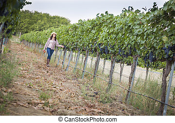 Young Female Farmer Inspecting the Grapes in Vineyard