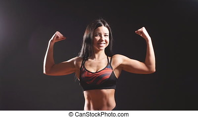 Young female fitness model posing in studio. Slow motion