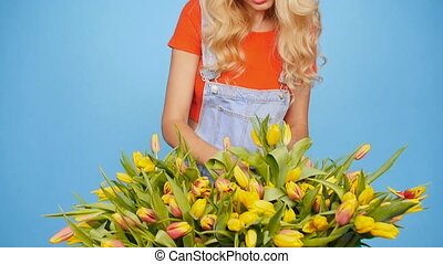 Young female florist with big box of yellow tulips -...