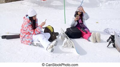 Young female friends relaxing with snowboards