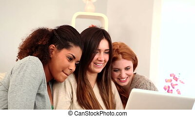 Young female friends using notebook