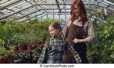 Young female gardener in apron and her cute daughter are dancing in greenhouse having fun. Happy family, gardening, parents and children concept.