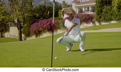 Young female golfer lining up a putt - Young female golfer...