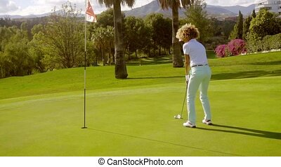 Young female golfer playing a putting shot on the green...