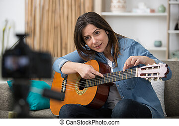 young female guitar blogger recording video tutorial