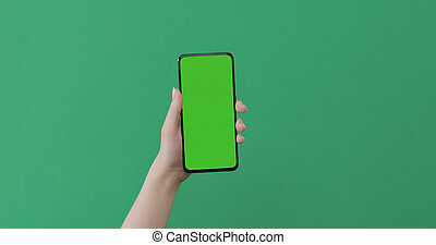 Young female hand hold smartphone with green screen on green background