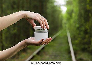 Young Female hands open a white jar of cream for face or body. organic natural skincare products on green natural background. Packaging of lotion or cream. Beauty cosmetic skin care concept