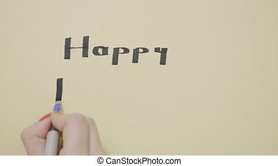 Young female hands writing happy birthday on a paper with black pen