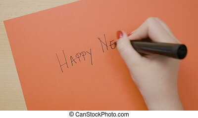 Young female hands writing happy new year on red paper with...