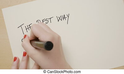 Young female hands writing the best way out is always through exclamation point motivational quote on white paper with a black marker