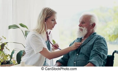 Young female health visitor examining a senior man in...