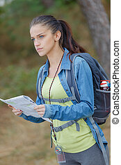young female hiker holding a map