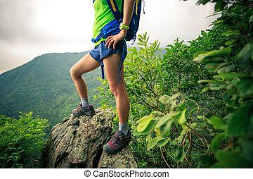 Young female hiker legs on mountain peak rock