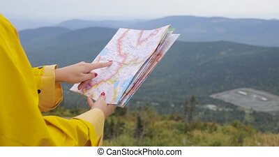 Young female Hiker looking at map from mountain top