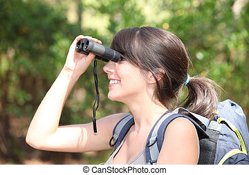 Young female hiker looking through binoculars