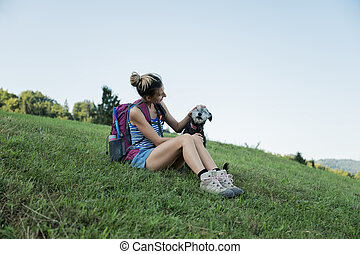 Young female hiker taking a break sitting in grass