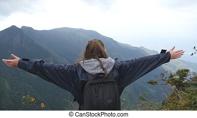 Young female hiker with backpack reaching up top of mountain and raised hands. Woman tourist in raincoat standing on the edge of beautiful canyon, victoriously outstretching arms up. Rear back view
