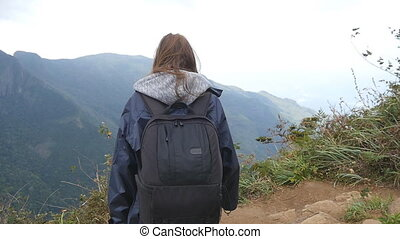 Young female hiker with backpack reaching up top of mountain and raised hands. Woman tourist in raincoat standing on the edge of beautiful canyon, victoriously outstretching arms up. Slow motion