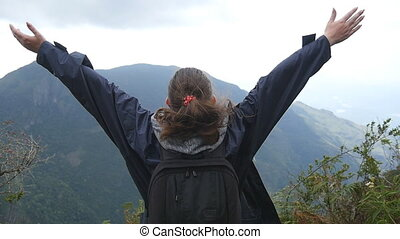 Young female hiker with backpack reaching up top of mountain and raised hands. Woman tourist standing on the edge of beautiful canyon, victoriously outstretching arms up. Slow motion Rear back view