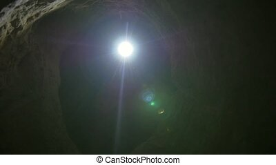 Young female hiker with flashlight explored the dark cave,...